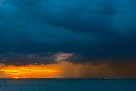 Ships in the sea on a background of clouds with rain during sunset / sunrise. The sun on the horizon. Rain at sea during sunset / sunrise. Contrast blue and yellow
