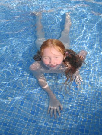 waterpool: Young girl having fun bathing in a pool.