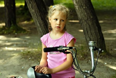 pigtail: Sad girl with bicycle in park