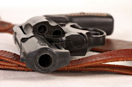 holster: small black revolver without holster is found on table