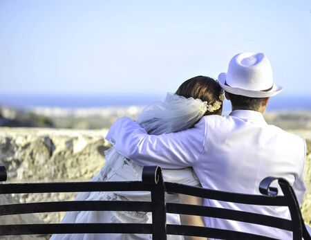 Summer wedding on Malta. Beautiful bride and groom on a cliff above the sea in a glamorous white wedding dress with scenic view to island, Malta. Happy woman, happy bride with scenic view in Malta.