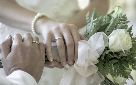 Hands of the bride and groom in white wedding dress with wedding rings on a bouquet of white roses. Daylight. Outdoors.