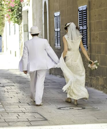 Summer wedding in old medieval city on Malta walking together by the ancient street in a glamorous white wedding dress 스톡 콘텐츠