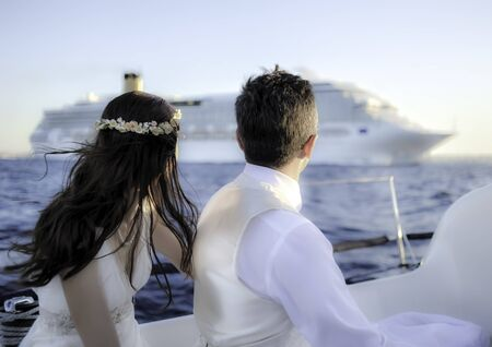 The groom and the bride look at cruise ship with the yachts on a sunny day. Daylight, outdoors.