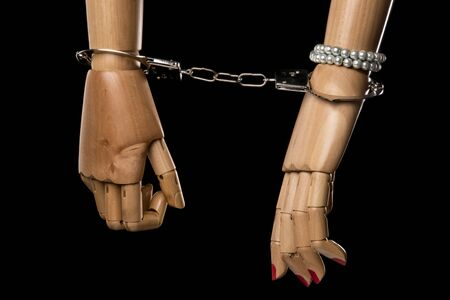restraints: Hand of  woman tying hand of man with handcuffs. Bondage or marriage. Isolated on black background. With copy space text. Studio Shot. Stock Photo