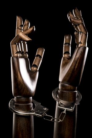 restraints: Handcuffs attach two black hands together. Isolated on dark background. Studio Shot. Vertical.