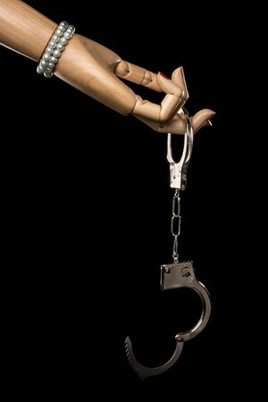 restraints: Hand of woman offers handcuffs. Love or jail. Isolated on black background. Studio Shot. With copy space text.