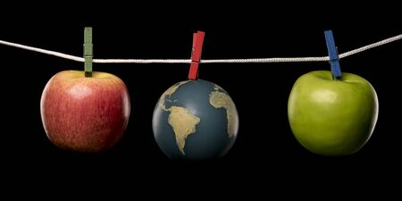 Earth and apples are hung from a rope with clothespins. Isolated on black background. Studio Shot.