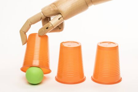 A wooden hand manipulates cups and balls in the game of monte