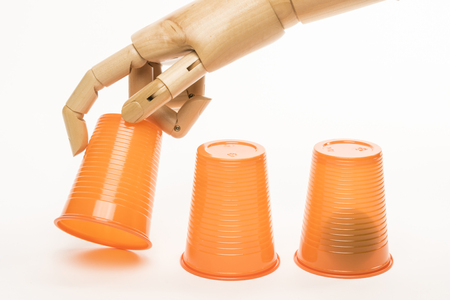 concealment: A wooden hand manipulates cups and balls in the game of monte