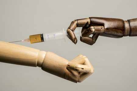 With a syringe, a black hand made an injection in a white arm. On gray background. With copy text.