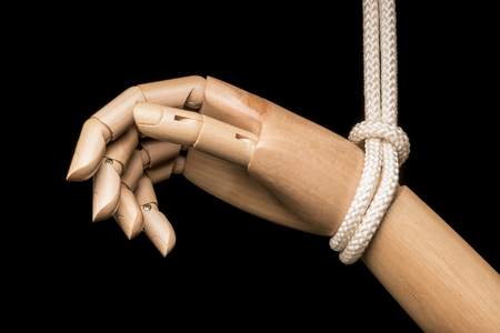 White hand attached on white rope in black background
