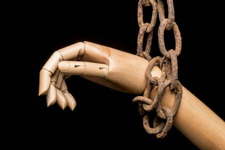 Hand attached to an old rusty chain on black background Stock Photo