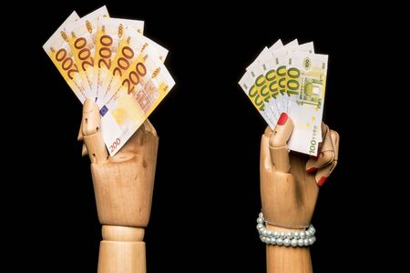 A mans hand waving more money than a womans hand. On black background. Stock Photo