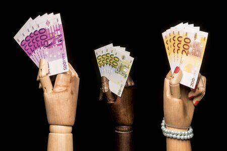 A mans hand waving more money than a womans hand ... but more than in the hand of a black. On black background. Stock Photo