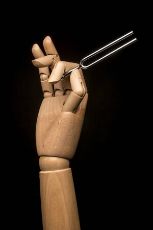 Wooden Hand sets the tone with a tuning fork in steel. In black background. Stock Photo