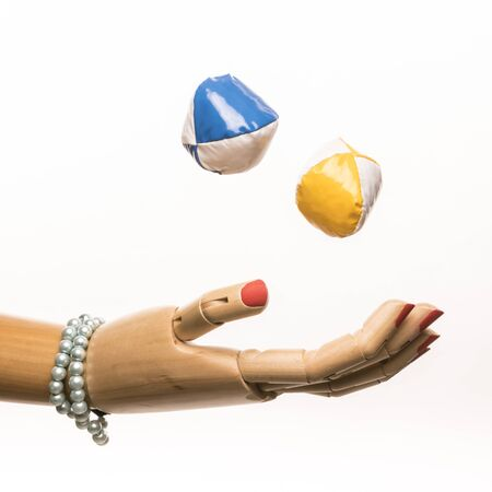 A womans hand with painted nails and bracelet juggles with balls. On white background. Stock Photo