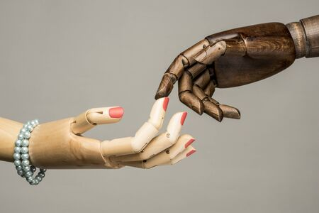 A white womans hand and a black mans hand touching the tip of a finger. On white background. On grey background.