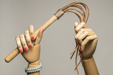 Womans hands brandishing a flogger. Cat with nine tails. On grey background.