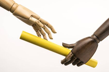 A black hand is handing over a white hand. The stick is yellow. On white background.