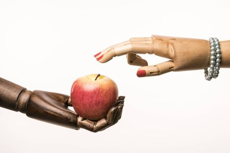 uñas pintadas: Black hand has an apple. Two fingers of the hand of a woman touching the apple. Interracial couple. The womans nails are painted red. She wears a pearl bracelet. Foto de archivo