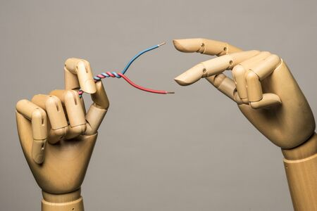 or electrocution: Two wooden hands manipulate electrical wire. On grey background.