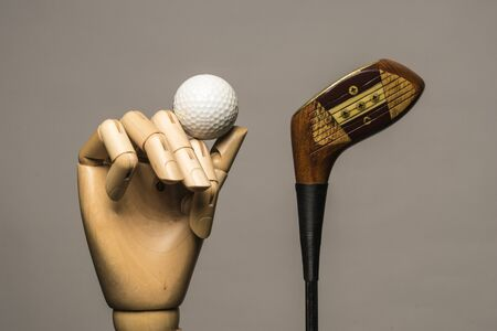 Golf ball, wood club and wooden hand. On grey bacground. Stock Photo