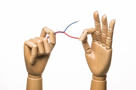 or electrocution: Two wooden hands manipulate electrical wire. On white background.