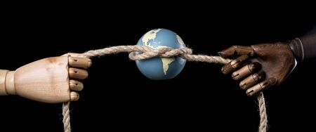 White hand and black hand strangle the Earth with a big rope. Isolated on dark background. With copy space text. Studio Shot. Stock Photo