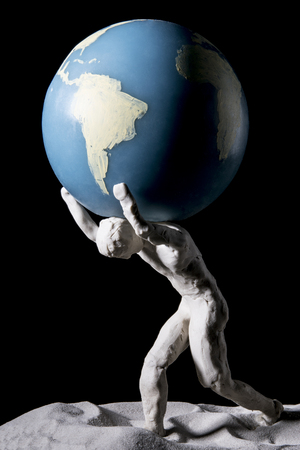 Titan Atlas supports the world on his shoulders. Isolated on black background. Studio Shot.