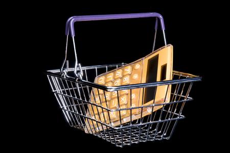Calculadora en la cesta de la compra. Studio Shot. Aislado en fondo negro. Foto de archivo