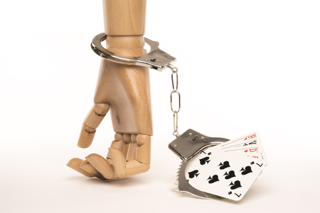 Hand tied to a card game by handcuffs. Game addiction metaphor. Isolated on dark background. Studio Shoot.