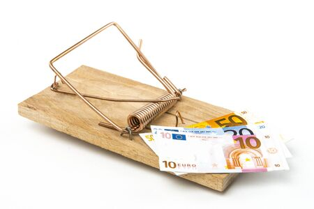 Money as bait in a mousetrap. Concept of the debt trap. On white background. Studio Shot.