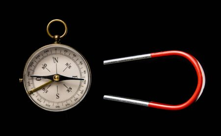 Magnet deviates a compass. Concept of fake news.  Isolated on black background. With copy space text. Studio Shoot.