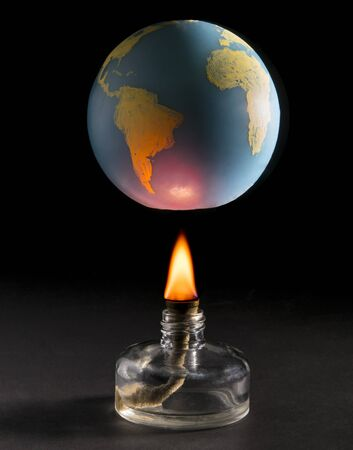 Laboratory stove warms the earth.Concept of global warming. Isolated on dark background. Studio Shot. Vertical