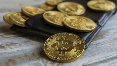Golden Bitcoins with leather wallet on a wooden table