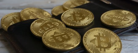 resplandor: Golden Bitcoins with leather wallet on a wooden table