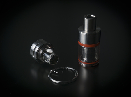 Repair,maintenance vaper device mod. Parts of modern vaporizer e-cig device,spare parts.Micro coil clearomizer.Modern ecig vape module closeup. Side view. Stock Photo