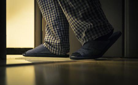 Volwassen man in pyjama loopt 's nachts naar een badkamer. Mens gezondheid concept Stockfoto