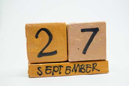september 27th. Day 27 of month, handmade wood cube calendar isolated on white background. autumn month, day of the year concept.