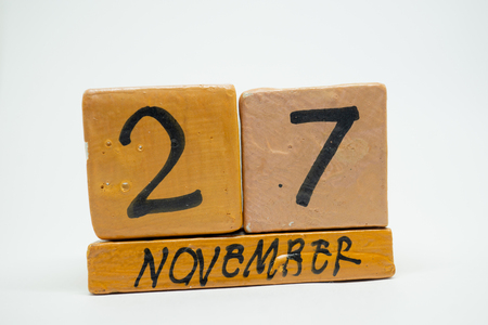 november 27th. Day 27 of month, handmade wood cube calendar isolated on white background. autumn month, day of the year concept.