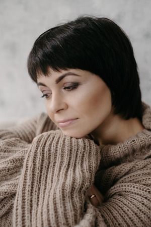 Gorgeous young brunette woman in warm knitted sweater posing on the bed