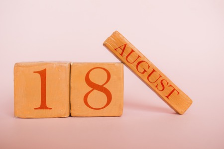 august 18th. Day 18 of month, handmade wood cube calendar  on modern color background. summer month, day of the year concept.