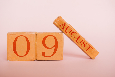 august 9th. Day 9 of month, handmade wood cube calendar  on modern color background. summer month, day of the year concept.