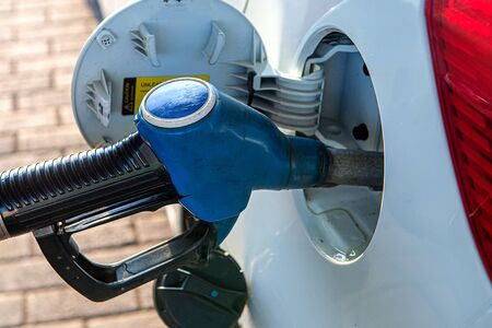 A gun for filling gasoline is inserted into the gas tank of the car. Holding fuel nozzle to refuel gasoline for car