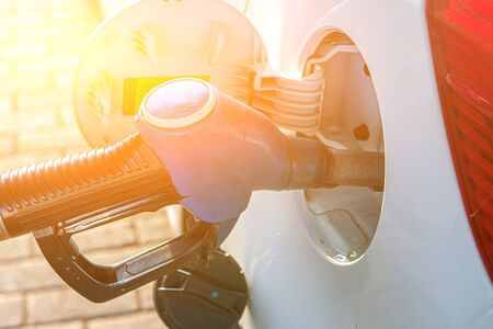 A gun for filling gasoline is inserted into the gas tank of the car. Holding fuel nozzle to refuel gasoline for car. Toned
