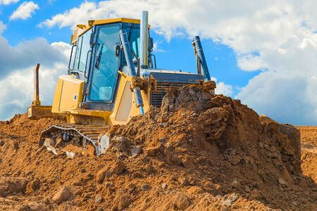 Crawler bulldozer - excavator with clipping path on a background with blue sky and clouds. work on construction site or sand pit.