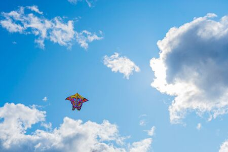 Beautiful colorful butterfly kite against the sky and clouds, freedom vacation travel concept.