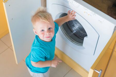 Portrait of a smiling toddler or baby boy in blue t-shirt playing with with washing machine