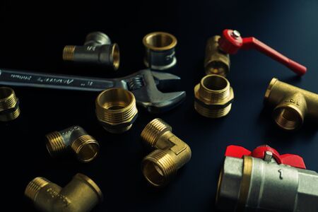 Plumbing equipment on a black background. Valves and wrench Standard-Bild